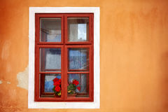 An old window with red flowers in orange wall. Royalty Free Stock Image