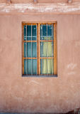 Old window, red wall. An old close wooden window on a red wall Royalty Free Stock Image