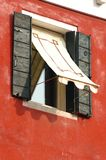 Old window on red wall,Venice, Italy Stock Photography