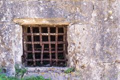 Old window with a rusty grating on ancient wall Stock Photography