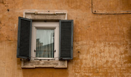 Old window set into an old, Ochre wall Stock Photos