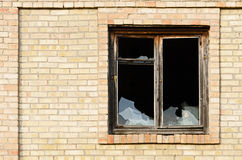 Old window with shattered glass. Old building with a broken glass window showing the darkness inside Royalty Free Stock Image