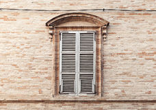 Old window shutters in ancient stone wall Stock Image