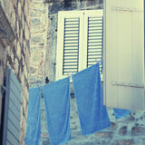 Old window with shutters and blue washing linen Stock Photo