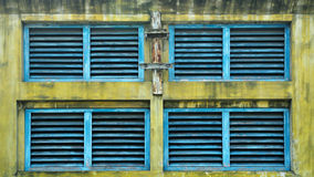 Old window shutters. Blue wooden shutters in yellow wall royalty free stock image
