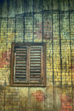 Old window with shutters. Window with closed shutters on the colorful wall of vintage wooden house as a background Stock Image