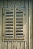 Old window with shutters. Window with closed shutters on the wall of vintage wooden house Royalty Free Stock Photos