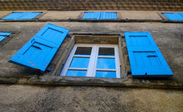 Rustic Window Shutters. The countryside of France has many old buildings with colorful window shutters. These blue shutters are on an old house in the city Stock Images