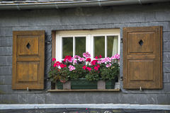 Old window with shutters and flower basket with Geranium flowers, Germany. Old window with shutters and flower basket full of Geranium flowers, Germany Royalty Free Stock Image