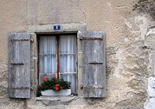 Old window and shutters in Nimes Switzerland. Old window and aged wooden shutters with flower-box full of red flowers against stone wall in Nimes Switzerland Stock Images