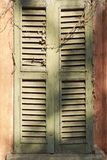 Old window with shutters in wood, ruined by time between light and shadows Stock Photo