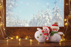 Old window sill with gold christmas lights and cute snowmen Royalty Free Stock Photography