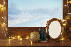 Old window sill with gold christmas lights. And empty vintage frame in front of dreamy and magical winter snow landscape background. Ready to put photography Stock Photography