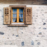 Old window in stone wall. Old square wooden window with shutters in stone rendered wall of Swiss Alpine chalet Stock Photography