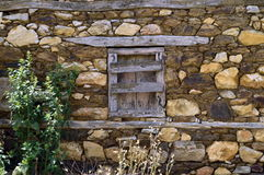 Old window in a stone wall. An old window in an abandonned stone house in Prespes, Greece Stock Photo