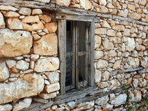 Old window in a stone wall. Old window in an abandonned house of traditional architecture in the greek region of Prespes Stock Photography