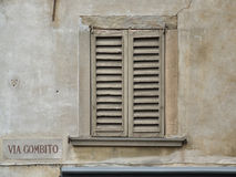 Old window in a town near Milan. Interesting old window with closed shutters - sad scenery, historic architecture, dark place, touristic town. Name of a street Royalty Free Stock Photos