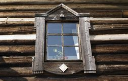 Old window on the wall of a wooden house. Stock Photo