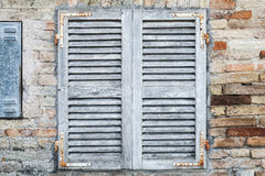 Old window with white closed wooden shutters. In brick wall, background photo texture Stock Photos