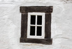 Old window on a white wall of house Royalty Free Stock Photo
