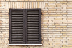 Old window with wooden shutters in brick wall Royalty Free Stock Image