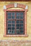 Old window on yellow building facade. With decorative brick frame and arch Royalty Free Stock Images