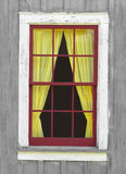 Old window with a yellow curtain. Outside view of an old red widow frame on a gray wood wall, with  yellow curtains Royalty Free Stock Image