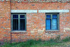 Two old windows behind a lattice on a brick wall Stock Images