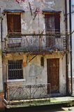 Old decaying italian architecture in brown tones. Old windows and doors and decaying cracking terracotta brown plaster balconies with dark railings not shutters stock images