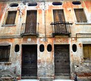 Old decaying italian architecture in brown tones. Old windows and doors and decaying cracking terracotta brown plaster balconies with dark railings not shutters stock image