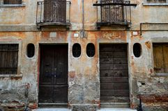 Old decaying italian architecture in brown tones. Old windows and doors and decaying cracking terracotta brown plaster balconies with dark railings not shutters stock photos