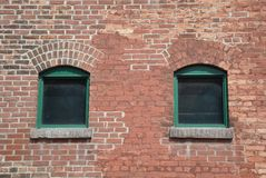 Old windows. Old glass windows in a brick walled building royalty free stock images