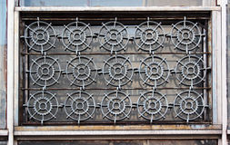 Old windows with iron grate shaped like a cogwheels Stock Photo