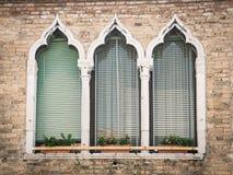 Old windows on a medieval palace facade in Verona. Stock Photos