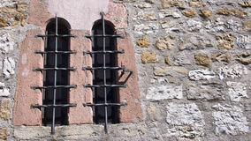 Old Windows with Metal Bars. Old windows on a stone wall with metal bars stock photo