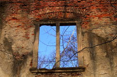 Old windows and wall. Discarded ruin with old windows and wall, industrial window in concrete wall, blue sky look in window Royalty Free Stock Image