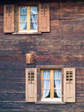 Old windows in wooden chalet. Old square wooden windows with shutters in wooden Swiss Alpine chalet Royalty Free Stock Images