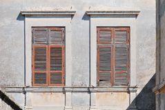 Old windows with wooden shutters from the sun. Traditional windows of the Mediterranean. The facade of an old Greek house with windows Royalty Free Stock Photos