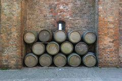 Old wine barrels stacked against a rustic brick wall stock photos