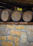 Old wine barrels on stone wall Stock Photo
