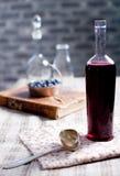 Old wine bottle with homemade berry vinegar. Old, vintage wine bottle with homemade blackcurrant, blueberry and blackberry vinegar stock photography