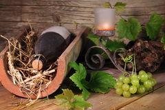 Old wine bottle on a tile with grapes Royalty Free Stock Photos