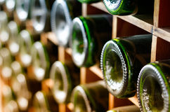 Old wine bottles stacked on wooden racks Royalty Free Stock Photography