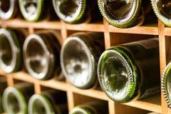 Old wine bottles stacked on wooden racks Stock Photos