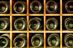 Old wine bottles stacked on wooden racks Stock Photography