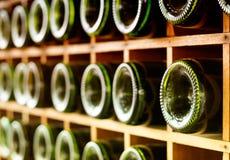 Old wine bottles stacked on wooden racks Stock Images