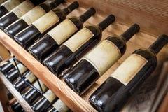 Old wine bottles on the wine shelf. Royalty Free Stock Image
