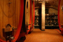 Old wine cellar. With big wine barrels andd old bottles Stock Images