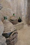 Old wine draided bottles in a cellar. Of antique castle Ischia Stock Photo