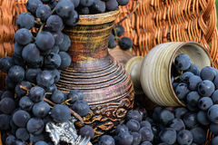 Old wine pitcher and clay glass, winemaking emblem and a cork. Old wine pitcher and clay glass surrounded by black grapes in a wicker basket with metal stock photography